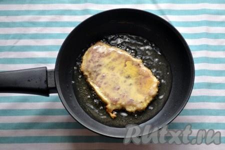 Огонь делаем ниже среднего. Обильно обмакиваем отбивную из свинины в кляр и выкладываем мясо на сковороду. Обжариваем с двух сторон по 2-3 минуты.