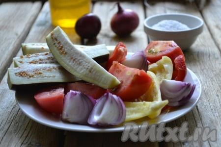 Лук очистить. У баклажанов и помидоров удалить хвостики. Болгарский перец очистить от семян. Помидоры, лук, баклажаны и перцы разрезать на 4 части.