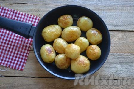 Очищаем картофель от кожуры (лучше брать картошку некрупную, примерно одинакового размера), моем и выкладываем на разогретую сковороду с небольшим количеством масла, обжариваем до золотистой корочки со всех сторон под закрытой крышкой. Периодически необходимо помешивать, делая круговые круги сковородой, не открывая крышку.