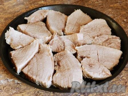 Когда свинина сварится, вынуть ее из бульона, немного остудить и нарезать на порционные кусочки. Форму для выпечки слегка смазать маслом. Выложить мясо.