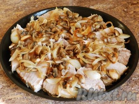 Поверх свинины разложить обжаренные грибы с луком.