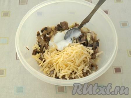 Шампиньоны выложить в подходящую посуду, дать остыть, натереть к ним половину сыра и смешать со сметаной.
