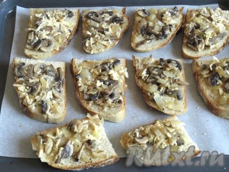 Кусочки хлеба намазать грибной массой и разложить на противне, застеленном бумагой.