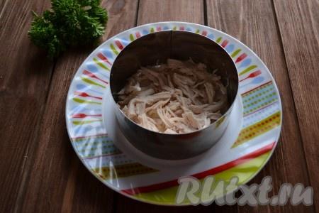 Смазываем дно тарелки крем-сыром (можно заменить сметаной или майонезом), ставим формовочное кольцо, выкладываем 1/3 куриного мяса.