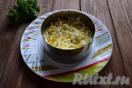 Выкладываем следующим слоем половину яиц и смазываем крем-сыром (если промазываете слои не крем-сыром, а сметаной, то слой яиц нужно посолить).
