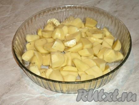 Картофель очистить, вымыть, нарезать крупными кубиками, посолить, поперчить и выложить в жаропрочную форму, смазанную растительным маслом.