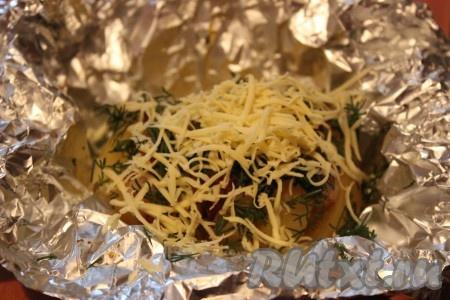Горячий картофель аккуратно развернуть и сразу же посыпать мелко рубленной зеленью и натертым на мелкой терке сыром.