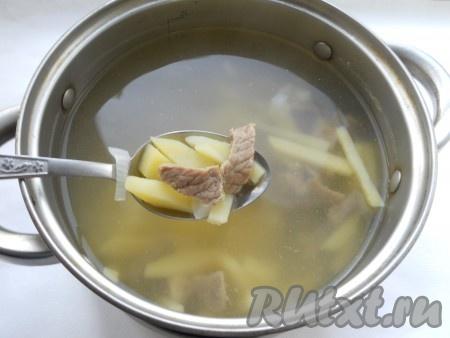 Добавить картофель к вареному мясу в кастрюлю, варить все вместе 25 минут.