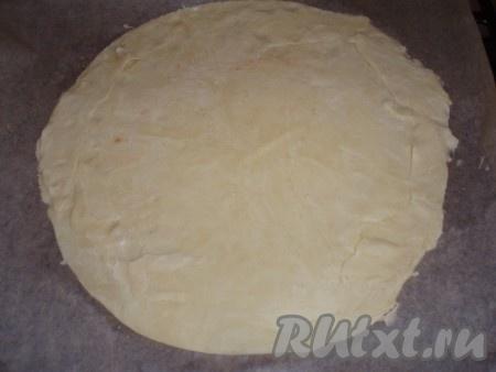 Охлажденное тесто раскатать на бумаге для выпечки в круг, диаметром примерно 30 см, и перенести на противень.