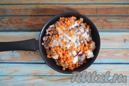 Лук и морковь очистить, нарезать мелкими кубиками и выложить в сковороду поверх мяса.