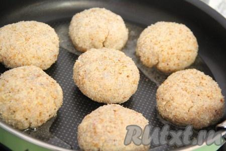 Масло влить в сковороду и поставить на огонь. Выложить котлеты из минтая с салом в сковороду.