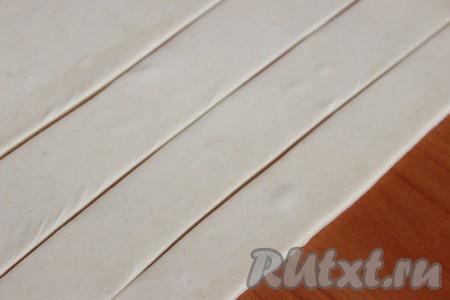 Размороженное тесто слегка раскатать и разрезать на тонкие полоски шириной, примерно, по 2-2,5 сантиметра.