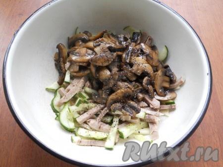 К языку добавить нарезанный соломкой огурец и очищенное от кожуры и семян яблоко. Сюда же добавить шампиньоны. Посолить салат и поперчить.