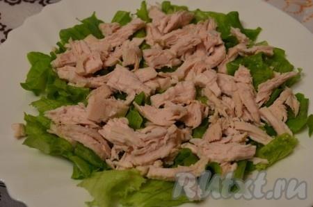 Отварное куриное филе нарезать произвольно. Выложить на листья салата.