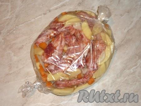 В рукав для запекания сложить картошку, лук и морковь, посолить, добавить специи по вкусу и перемешать. Сверху на овощи выложить свиные рёбра.Рукав завязать с двух сторон и отправить в разогретую духовку запекаться при температуре 180 градусов на 60 минут.