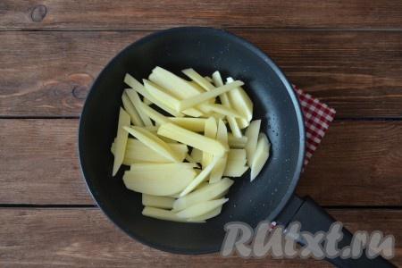 Картофель очистить, вымыть, нарезать соломкой и выложить на полотенце, чтобы ушла лишняя влага. На разогретую сковороду влить масло и нагреть его на протяжении 1 минуты. Выложить картошку.