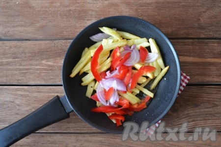 Лук очистить, вымыть и нарезать тонкими-тонкими полукольцами. Из перца удалить плодоножку и семена, вымыть и нарезать тонкой соломкой. Выложить овощи в сковороду, перемешать и обжарить вместе с картофелем буквально 1 минуту.