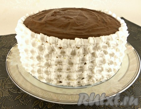 Верх бисквитного торта покрыть растопленной шоколадной массой и дать застыть ей в холодильнике. Далее белковым кремом украсить бока торта с помощью кондитерского шприца или мешка с насадкой на ваше усмотрение.