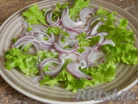 В тарелку нарвать руками листья салата. Добавить лук.