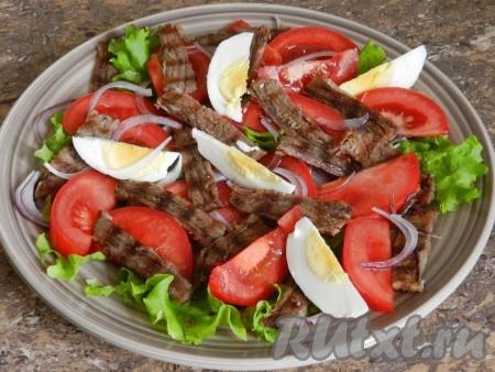 Яйца очистить, нарезать на четвертинки и добавить в салат из говядины, лука и помидоров. Посолить.