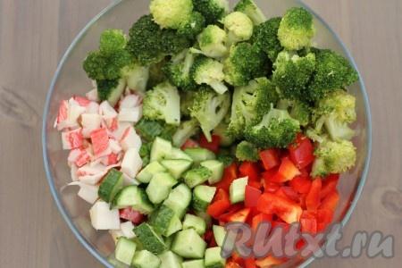 Болгарский перец очистите от семян. Крабовые палочки, болгарский перец и огурцы нарежьте крупными кубиками, добавьте соцветия брокколи и перемешайте салат.