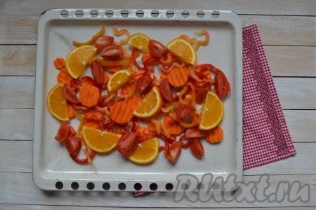 Половину лимона и половину апельсина нарезать тонкими полукольцами. Перцы вымыть, удалить плодоножки и семена, нарезать соломкой. Очистить морковь и нарезать тонкими колечками. Вымыть помидоры и разрезать на 4 части. Все подготовленные овощи и цитрусовые выложить на противень при желании противень можно смазать растительным маслом).