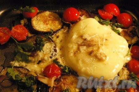 Добавить кусок сыра, порезанную зелень, посолить, поперчить. Отправить баклажаны с сыром, помидорами и луком запекаться в духовку при температуре 220 градусов до запекания сыра.