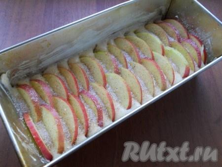 Бока формы для кекса смазать сливочным маслом, дно застелить пергаментом. Выложить тесто в форму размером 25х11 см. Яблоки нарезать тонкими дольками и разместить их вертикально по верху теста. Посыпать яблоки сахаром с корицей.