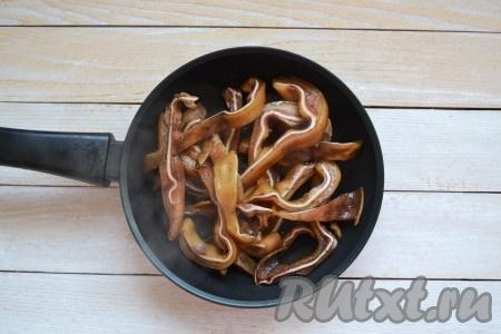На разогретую сковороду влить масло и через минуту выложить уши. Периодически помешивая, обжарить 2 минуты. Влить половину соуса, в котором мариновались свиные уши, и продолжить обжаривать еще 10-15 минут, иногда перемешивая. За это время должна выпариться вся жидкость со сковороды, а сами ушки поджарятся до красивого румяного цвета.