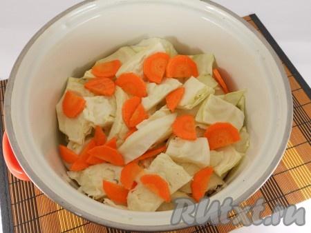 Капусту нарезать крупными частями. Лучше взять капусту небольших размеров и разрезать ее на 6-8 частей. Если капуста крупная (как у меня) - резать просто крупными кусками. Поместить капусту в кастрюлю. Сверху выложить нарезанную тонкими полукружочками морковь.
