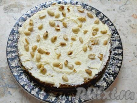 На него - белый корж, смазать кремом и выложить целый, предварительно обжаренный и очищенный, арахис.