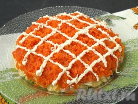 Натереть на тёрке морковь. Выложить морковь сверху ветчины и смазать майонезом.