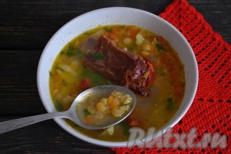 Разлить гороховый суп с копчеными ребрышками, приготовленный в мультиварке, по тарелкам, добавить измельченную зелень и подать на стол.