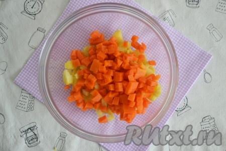 Морковь сварить в кожуре, затем остудить, очистить, нарезать мелкими кубиками и выложить к картошке.