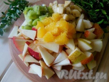 Апельсин очистите от кожуры, разделите на дольки, при желании дольки можно очистить от плёночек. Яблоки и груши очистите от семечек (шкурку можно оставить). Очищенные киви и бананы, апельсин, яблоки и груши нарежьте небольшими кусочками.