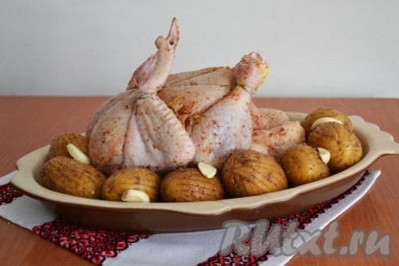 Выложить в форму для запекания целую курицу и картофель (при желании форму можно смазать маслом). Сверху картофеля положить тонкие пластины нарезанного чеснока.