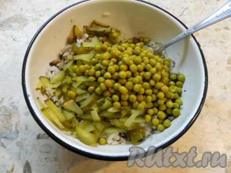Далее выложить в салат к рису и грибам нарезанные небольшими кусочками маринованные огурцы и консервированный горошек.