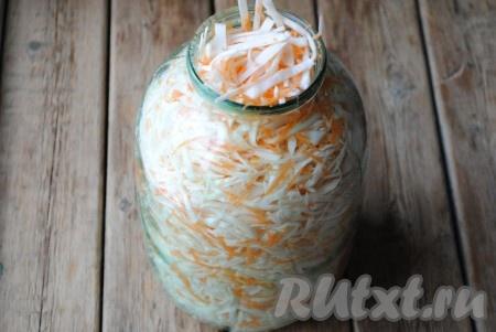 В банку выложить капусту с морковкой и хорошо утрамбовать.