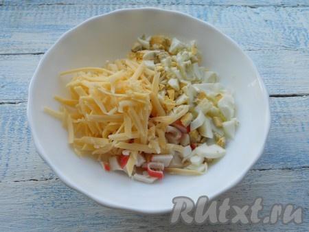 К крабовым палочкам добавить рубленное вареное яйцо и натертый на средней терке твердый сыр.