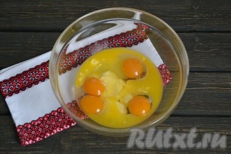 В глубокой миске соединить подтаявшее сливочное масло и 4 куриных яйца. Если использовать домашние яйца - в результате кексы будут насыщенного желтого цвета.