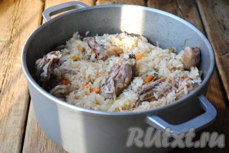 Тушить капусту с мясом и рисом на небольшом огне под крышкой до готовности риса. Время приготовления будет зависеть от сорта риса. Я готовила около 20 минут. В конце приготовления в блюдо можно добавить измельчённую зелень. Снять казан с плиты и дать немного солянке настояться.