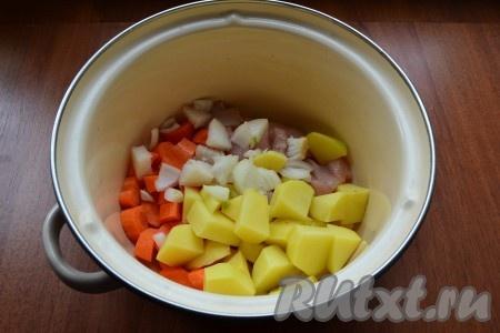 Добавить в кастрюлю очищенные и нарезанные кубиками картофель и репчатый лук.