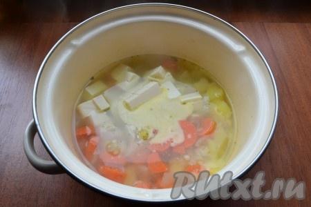 Влить в кастрюлю воду и поставить на огонь, все посолить по вкусу и варить на слабом огне до готовности (около 35-40 минут). Далее добавить в суп нарезанный кубиками плавленый сырок, сливочное масло, специи, варить до расплавления сыра.