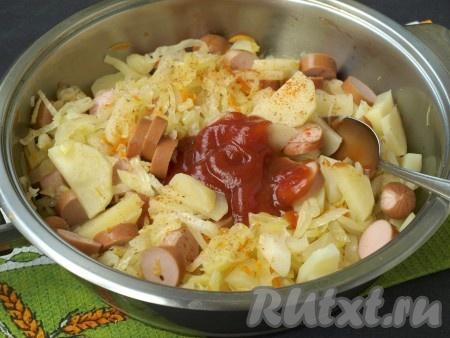 Посыпать блюдо молотым перцем, добавить томатный кетчуп, перемешать, снова накрыть сковороду крышкой и тушить капусту с картошкой и сосисками 8-10 минут.