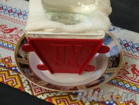 Поставить пасочницу в тарелку для стекания сыворотки, края подвернуть наверх. Сверху поставить тарелку и на неё груз весом 500 грамм. Всё вместе поставить в холодильник на 12-15 часов. За это время слить сыворотку 2-3 раза.
