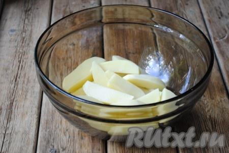 Нарезать картофель крупными дольками. Сложить его в миску, которая подходит для использования в микроволновой печи.