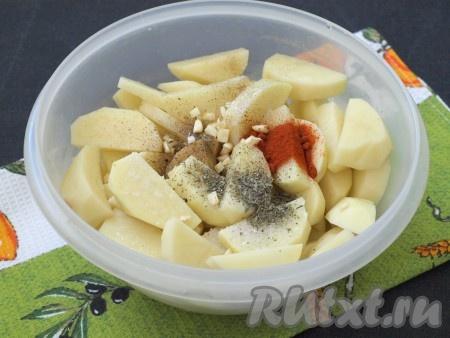 Нарезать ломтиками очищенный картофель, сложить в миску, добавить приправу, базилик, паприку, соль и измельчённый чеснок. Я чеснок нарезала кубиками, можно пропустить через пресс.