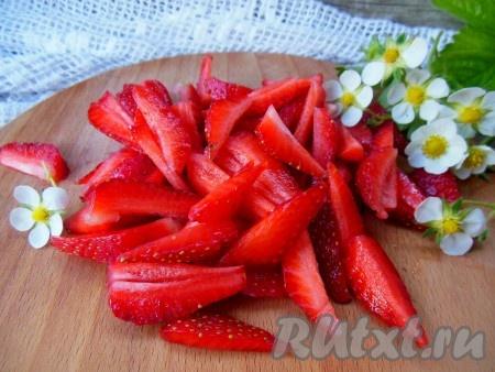 Удалите чашелистики. Разделите клубнику на две, примерно, равные части. Одну часть ягод нарежьте на небольшие кусочки.