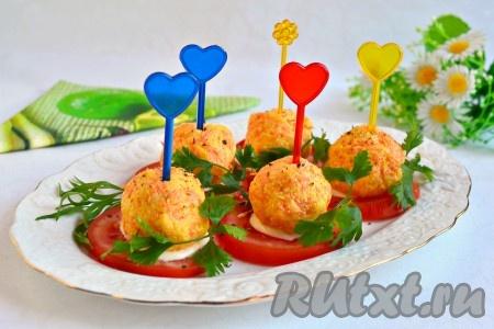 На помидоры выложить подготовленные перепелиные яйца в сыре, поперчить немного, украсить зеленью и вставить шпажки.