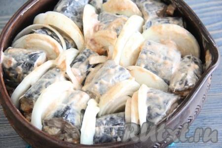Кусочки рыбы выложить в жаропрочную форму, между кусочками рыбки выложить лук. На дно формы налить немного воды. Запекать скумбрию в разогретой духовке при температуре 200 градусов, примерно, 25 минут.
